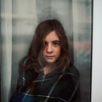 Girl wrapped in a tartan blanket at a rain covered window