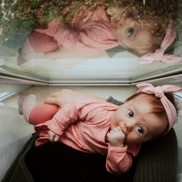 Birdseye view of a baby girl in pink at a window sucking on her hand.