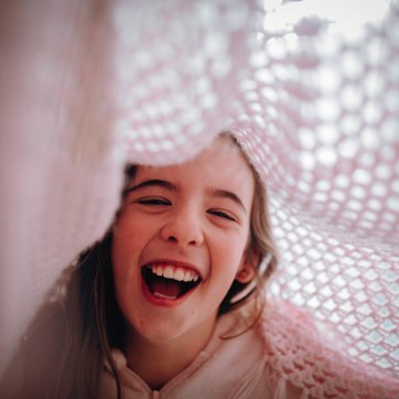 Girl underneath pink crochet blanket laughing