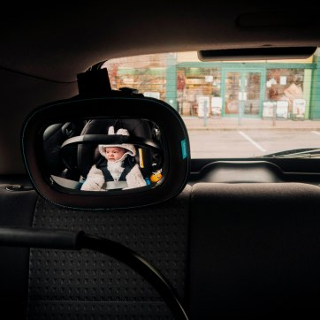 Photograph of a car seat mirror reflecting a baby in white in a car seat gazing out of the window
