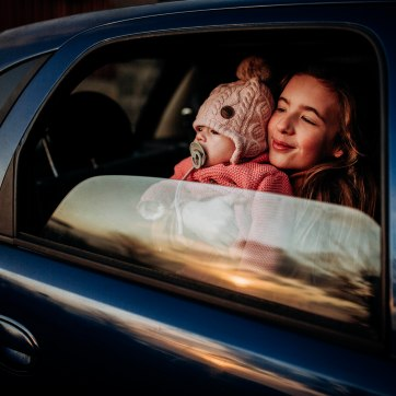 Sisters watching the sunset through an open window in a blue car