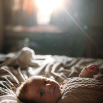 Newborn on the bed bathing in sunlight from the window