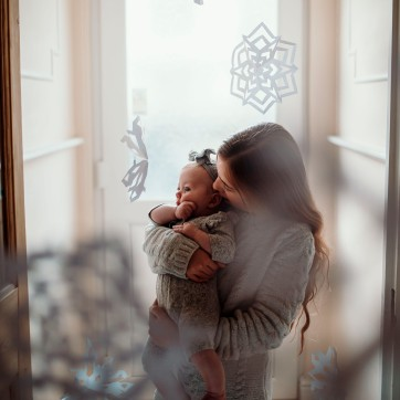 Older sister holding baby sister in a front door way in grey clothing surrounded by paper snowflakes