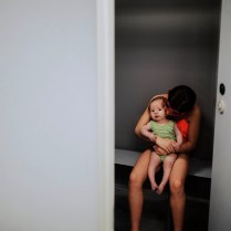 Two girls embrace in a changing cubicle, one newborn in green and older girl in pink