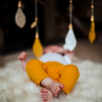 baby toes on a fur rug with hanging leaves