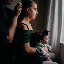 Mother gently caressing her daughter's hair who has her baby sister on her lap by the window