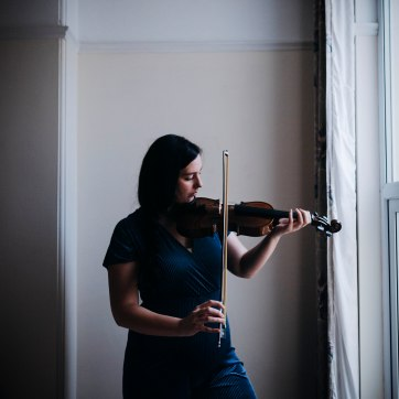 Girl in blue playing a violin by the window