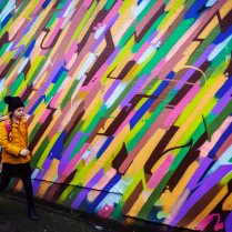 Girl in yellow jacket walking in front of a multicoloured wall
