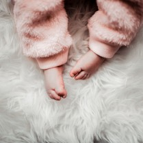 Baby toes on a white fur rug with pink fluffy trousers