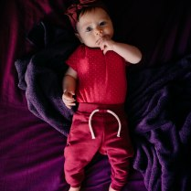 Birdseye view of a baby girl on purple bedding wearing pinks and purples